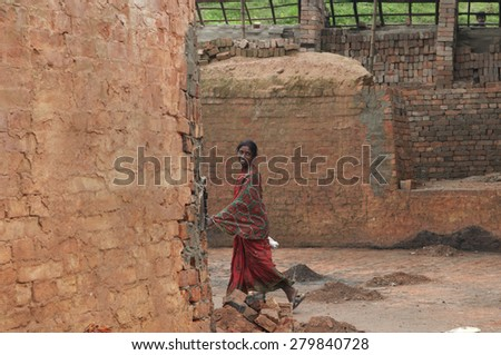 KOLKATA - OCTOBER 26: A woman worker passing by inside a brick factory where she work and stay under difficult conditions  on October 26,2014 in Kolkata,India. - stock photo