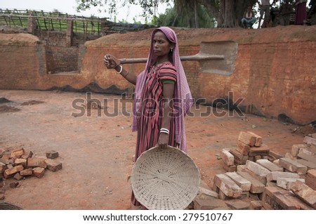 KOLKATA - OCTOBER 26 : A woman worker stepping inside a brick factory to work before the production season begins on October 26, 2014 in Kolkata , India.