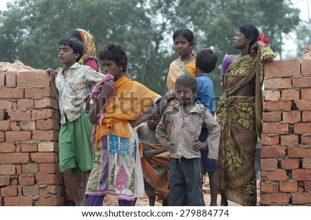 KOLKATA -OCTOBER 26 :Women and kids standing inside a brick factory where they work in tough conditions although India is the the second largest brick industry on October 26, 2014 in Kolkata , India.  - stock photo