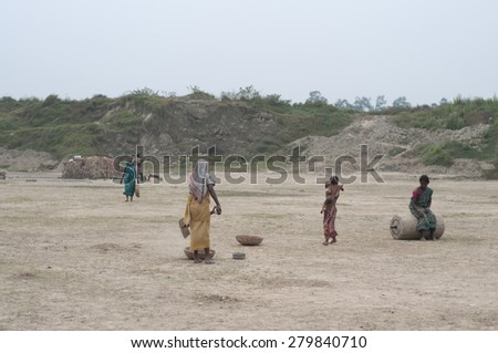 KOLKATA - OCTOBER 26 : Women workers and their families working in a brick factory where they work for minimum wages and without any kind of social security on October 26, 2014 in Kolkata , India. - stock photo