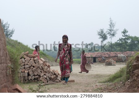 KOLKATA - OCTOBER 26 : Women workers coming out of her house and walking towards the brick factory on October 26, 2014 in Kolkata , India. - stock photo