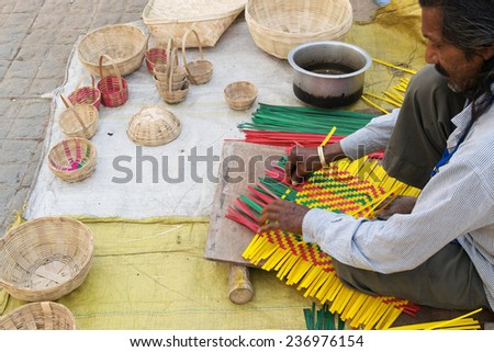 KOLKATA, WEST BENGAL , INDIA - NOVEMBER 23RD 2014 : Unidentified man making wicker baskets, artworks of handicraft, on display during Handicraft Fair in Kolkata - the biggest handicrafts fair in Asia. - stock photo