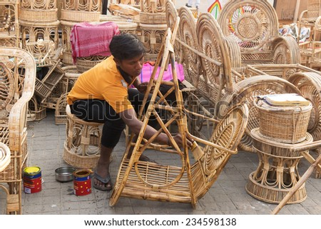 KOLKATA, WEST BENGAL , INDIA - NOVEMBER 23RD 2014 : Unidentified person polishing Cane furnitures , handicrafts on display during the Handicraft Fair in Kolkata - the biggest handicrafts fair in Asia. - stock photo