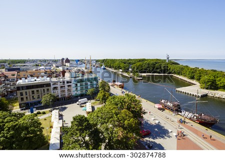 KOLOBRZEG, POLAND - JULY 17, 2015: The port canal leading to the seaport and the panorama of the City as seen from the lighthouse, by the data of 2014 the city is inhabited by about 47,000 residents - stock photo