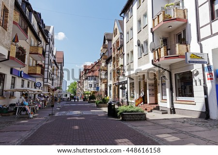 KOLOBRZEG, POLAND - JUNE 23, 2016: Residential buildings along one of the streets of the Old Town district, on the ground floor there are many retail services