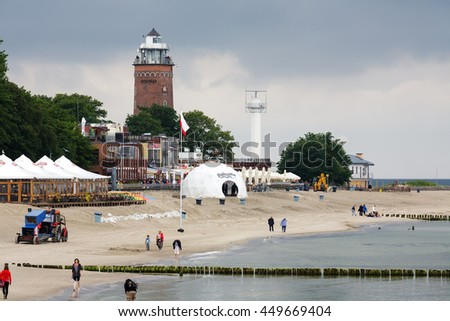 KOLOBRZEG, POLAND - JUNE 21, 2016: Sandy beach in preparation before the holiday season, tourists are walking along the shore and in the background made of brick the lighthouse can be seen - stock photo