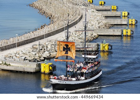 KOLOBRZEG, POLAND - JUNE 22, 2016: Stylized double deck cruise ship named The Pirate enters the port, on board the many tourists returning from a trip on the waters of the Baltic Sea - stock photo