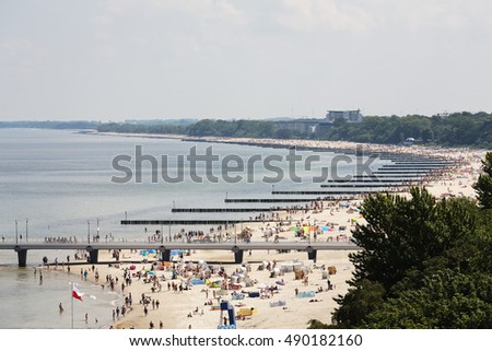 KOLOBRZEG, POLAND - JUNE 22, 2016: The coastline of the Baltic Sea, along many breakwaters were placed that protect the beach against effects of sea waves. Many sunbathers can see there.