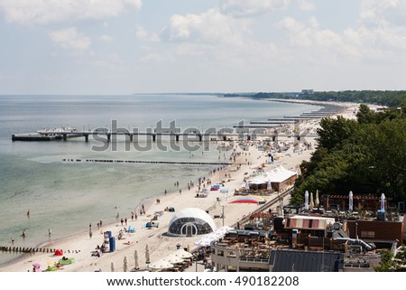 KOLOBRZEG, POLAND - JUNE 22, 2016: The coastline of the Baltic Sea. The pier over the Baltic Sea waters and many breakwaters were placed that protect the beach against effects of sea waves can be seen