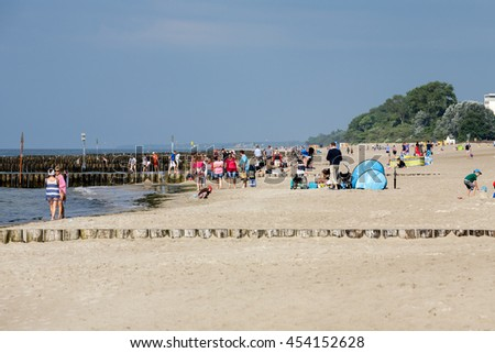 KOLOBRZEG, POLAND - JUNE 29, 2016: Unidentified vacationers enjoying the sunshine on the sandy beach of the Baltic Sea - stock photo