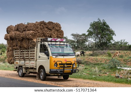 Konapuram Pirivu, India - October 24, 2013: A beige-yellow Tata Pickup truck is overloaded with bales of jute and parked along rural road under blue sky. Goats and green foliage. In Tamil Nadu.