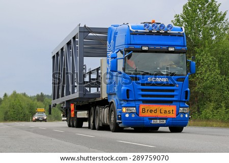KONGINKANGAS, FINLAND - JUNE 20, 2015: Scania truck hauls a wide load. The abnormal transport permit is required, if any dimension of the transport exceeds the free dimension limits. - stock photo