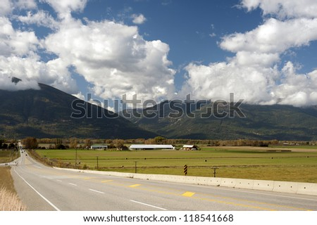 Kootenay Mountains with the farm, highway and fields - stock photo