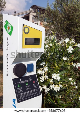KOPER, SLOVENIA - JULY 9, 2016: Photo showing detail of an e-mobile charging station on public parking lot together with oleander decorating bush.