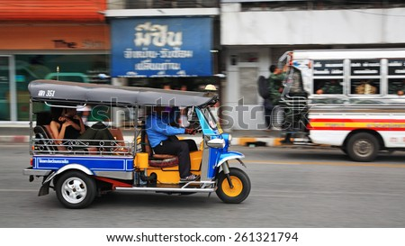 KORAT, THAILAND - JULY 18, 2014: tuk tuk taxi with passengers transport in the city. Tuk tuks can be hired from as little as $1 or B30 a fare for shop trips. - stock photo