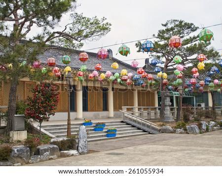 korean building with lanterns in park during cherry blossom festival, Gyeongju, South Korea - stock photo