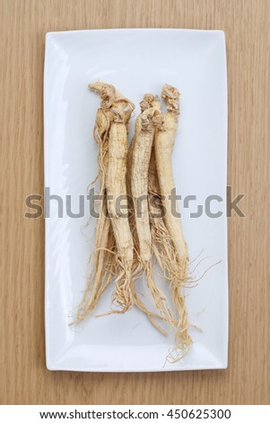 Korean dry ginseng roots on wood background. - stock photo