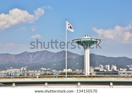 Korean flag and traffic control tower with clouds, mountain and blue skies. - stock photo