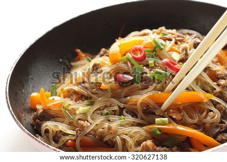 Korean food, carrot and cellophane stir fried Japchae on frying pan - stock photo