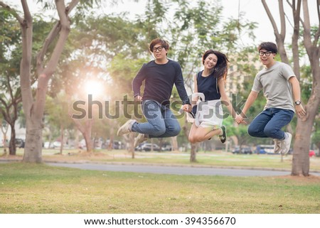 Korean friends holding hands when jumping outdoors - stock photo