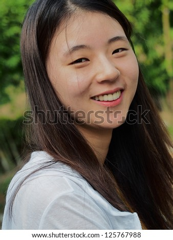 Korean girl smiling showing teeth.
