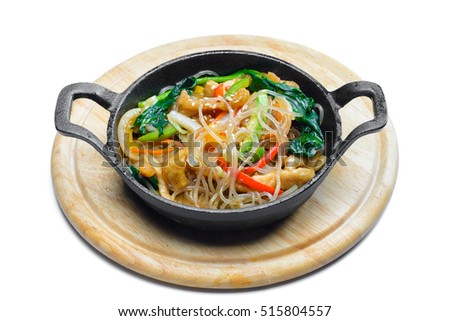 Korean rice noodle with vegetables on frying pan on white background