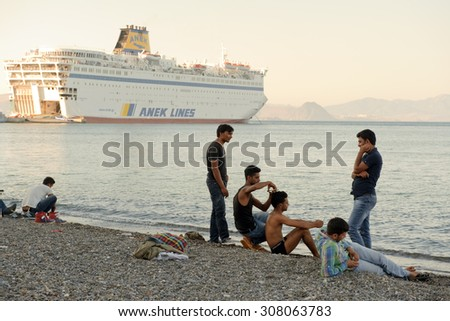 Kos, Greece - August 14, 2015: Greece-Europe-Migrants. Group of young migrants sitting of the beach and cutting the hair on Greece island Kos in front of ferry Eleftherios Venizelos.