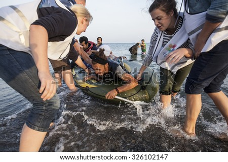 Kos, Greece - October 11, 2015: Volunteers are giving a hand to the immigrants from Afghanistan who arrived to Kos island from Turkey on a dinghy boat