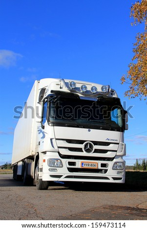 "KOSKI, FINLAND - OCTOBER 20: White Mercedes-Benz Actros truck with trailer parked on October 20, 2013 in Koski, Finland. Mercedes-Benz Actros wins Ireland's first ""Truck of the Decade"" award. - stock photo"