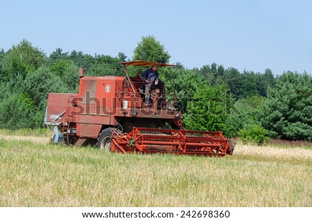 KOSMIDRY, POLAND - July 29, 2013 The combine moves to a field and collects wheat closeup
