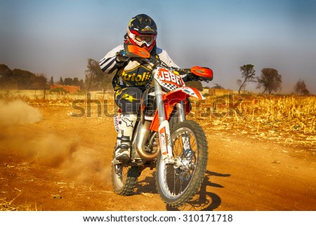 KOSTER, SOUTH AFRICA - July 11:  Africa-Offroad Racing Rally,  on July 11, 2015 at Koster, North West Province, South Africa.  HD - Junior Motorbike kicking up trail of dust on sand track.  - stock photo