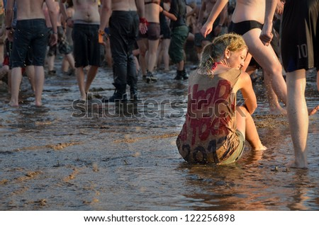 KOSTRZYN NAD ODRA, POLAND - AUGUST 4: Festival Przystanek Woodstock - woman sitting in the water in a crowd in front of the stage on August 4, 2012 in Kostrzyn Nad Odra, Poland. - stock photo