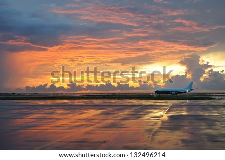 Kota Kinabalu (Borneo, Malaysia) airport in dramatic sunset light. Airplane ready to take off. Sunset sky reflection in wet runway after storm. - stock photo