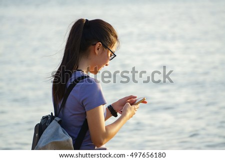 Kota Kinabalu Sabah Malaysia - Apr 12, 2015 : Unidentified teenager checking her smartphone while walking at the beach in Tanjung Aru Sabah. Smartphone is a must gadget among young asian teenager.