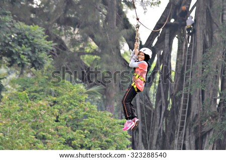 Kota Kinabalu, Sabah. September 30, 2015 : A young girl propelling on a flying fox at Outward Bound School Kinarut, Sabah. Flying fox is a small scale zip line that enable user to propell by gravity. - stock photo