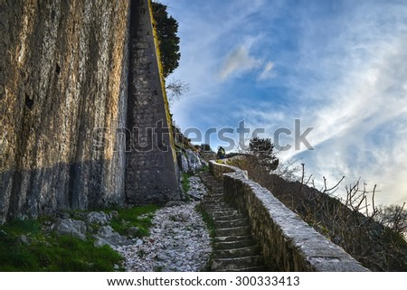 KOTOR, MONTENEGRO - JANUARY, 24: stairs leading up to the top of the ancient fortress of Kotor, Montenegro and a man climbing up, on January, 24, 2015