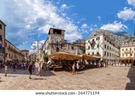 KOTOR,MONTENEGRO-JULY 18:Tourists walk on Square of Arms in Kotor Old Town the background many restaurant, on July 18, 2014 in Kotor, Montenegro.Kotor it is a very popular travel destination of Europe - stock photo