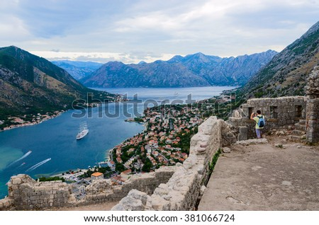 KOTOR, MONTENEGRO - SEPTEMBER 21, 2015: An unidentified man takes pictures of Kotor Bay being among of the ruins of the fortress of St. John (Illyrian fort) above the town of Kotor, Montenegro - stock photo