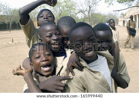 KOUPELA, BURKINA FASO - FEBRUARY 20 : A small group of pupils of the college Saint-Philippe have fun much to be photographed together, February 20, 2007 - stock photo