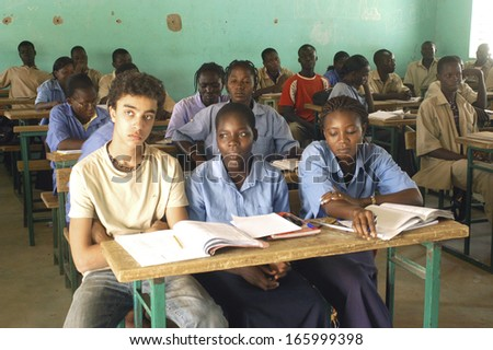 KOUPELA - BURKINA FASO - FEBRUARY 26, 2007: Visit of French schoolboy in Africa with the college Saint-Philippe. The pupils are in of a the same class level than in their French school. - stock photo