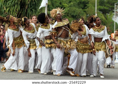 KOUROU, FRENCH GUIANA - FEBRUARY 15: These dancers participated in the main carnival parade February 15, 2009 in Kourou, French Guiana. The yearly theme contest is the GOLD & WHITE. - stock photo