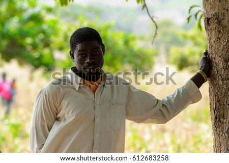 KOUTAMMAKOU, TOGO - JAN 13, 2017: Unidentified Togolese man stands near the tree in the village. Togo people suffer of poverty due to the bad economy.