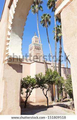 Koutoubia mosque with palms against clear blue sky, Marrakesh - stock photo