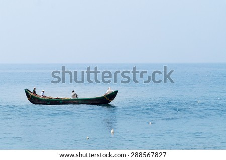 KOVALAM, INDIA - DEC 28, 2014: Traditional wooden fishing boats in the ocean. Kovalam. Kerala. India