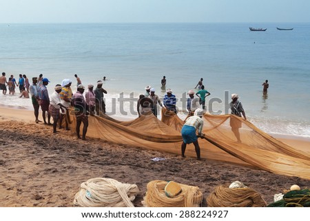 KOVALAM, INDIA - DEC 28, 2014: Unidentified Fishermen pull their fishing net on Samudra beach in Kovalam. Kerala. India