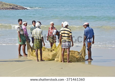 KOVALAM, TRIVANDRUM, KERALA, INDIA, FEBRUARY 03, 2016: Fishermen pulling up the net to find a disappointing harvest. A scene in the morning on the beach at Kovalam. - stock photo