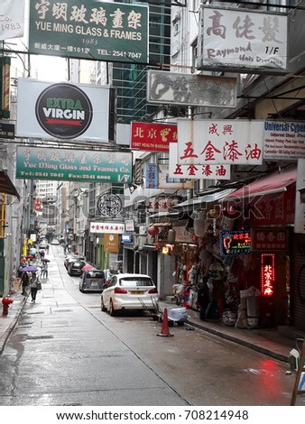 Kowloon, Hong Kong, Hongkong, China - Juli 23, 2017: street view nearby Yin Serviced Apartment, 97 Wellington St, Central, on a rainy day with a few pedestrians with umbrellas and many signs visible