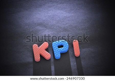 KPI (Key Performance Indicator) words on black background - stock photo