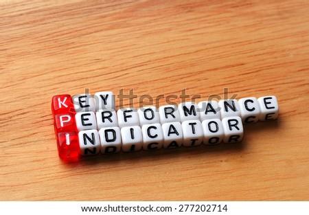 KPI Key Performance Indicator written on cubes on wooden background - stock photo