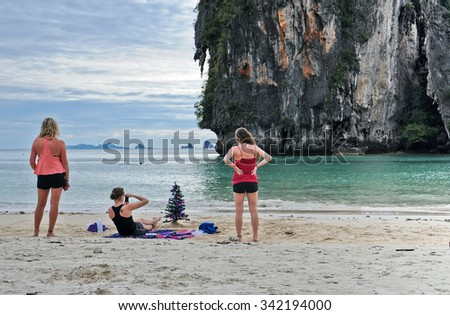 Krabi, Thailand - December 2, 2011: Girl dressed Christmas tree on the beach - stock photo